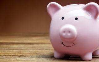 ceramic pink piggy bank on wooden background